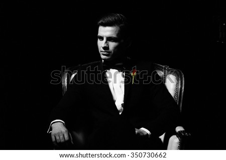 Portrait of man who sitting on chair, godfather-like character.