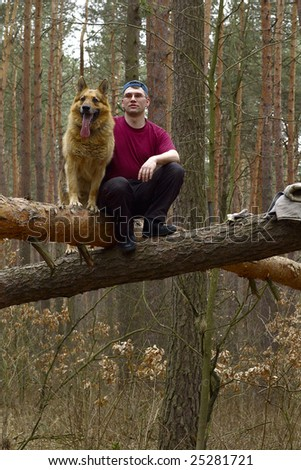 Portrait of man with a dog in the forest on the thrown-down trees