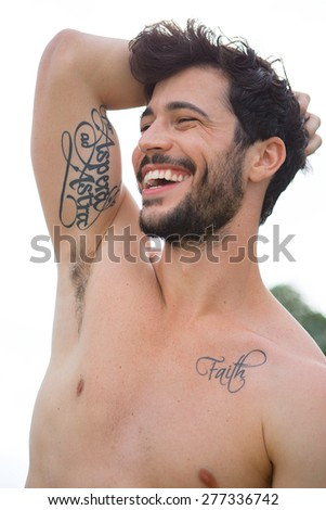 Portrait of man with bare chest and tatoos