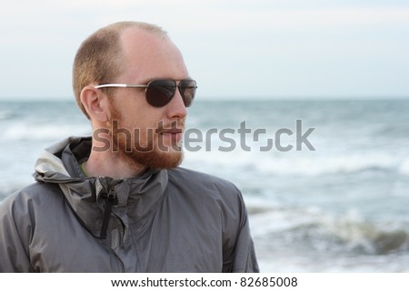 portrait of man with beard in sunglasses near sea