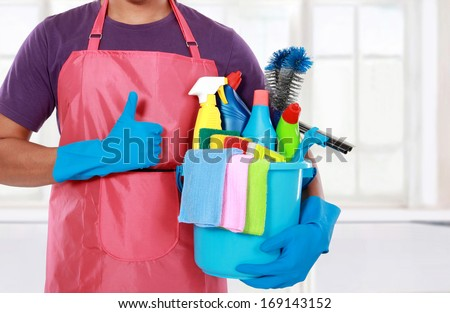 Portrait of man with  cleaning equipment showing thumbs up - stock photo
