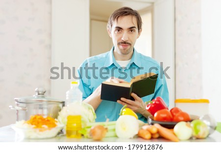 Portrait of man with cookbook in domestic kitchen at home - stock photo