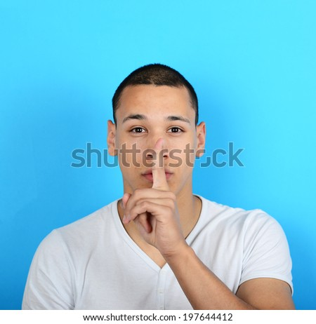 Portrait of man with gesture for silence against Portrait of man with gesture for silence against blue backgroundred background - stock photo