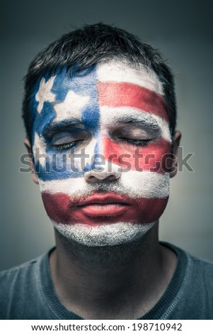 Portrait of man with USA flag painted on his face and closed eyes. - stock photo
