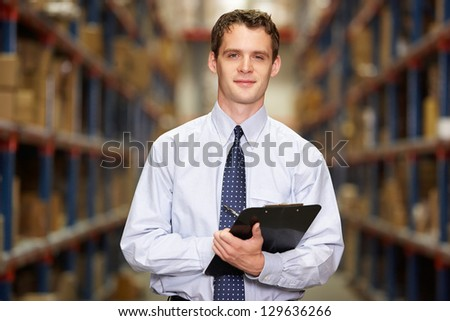 Portrait Of Manager In Warehouse With Clipboard - stock photo
