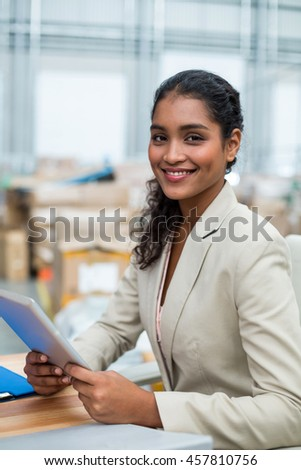 Portrait of manager is smiling and holding a tablet in a warehouse
