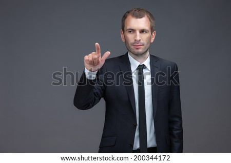 Portrait of manager pointing finger gestures, isolated on grey background. Concept of leadership and success - stock photo