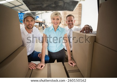 Portrait of managers smiling at camera behind the van in a large warehouse - stock photo