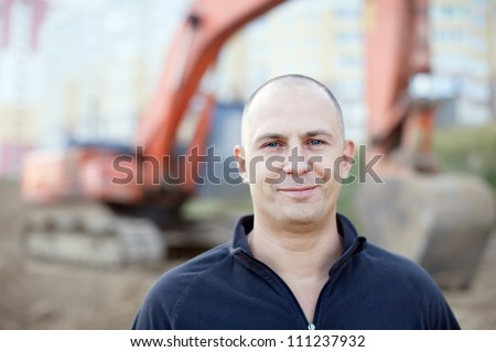 Portrait of manual worker at building site - stock photo