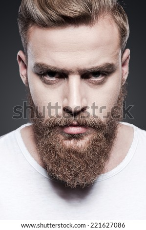 Portrait of masculinity. Portrait of handsome young bearded man looking at camera while standing against grey background - stock photo