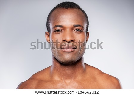 Portrait of masculinity. Portrait of young shirtless African man looking at camera while standing against grey background - stock photo