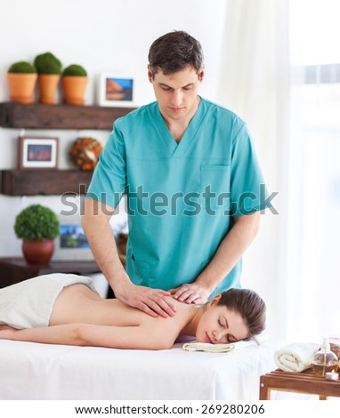 Portrait of massagist working with his client - stock photo