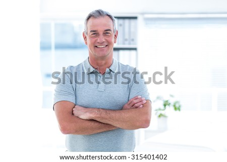 Portrait of masseur with arms crossed standing in spa - stock photo