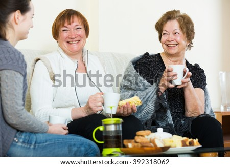 Portrait of mature and young women drinking tea and laughing - stock photo