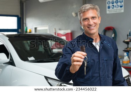 Portrait Of Mature Auto Mechanic In Garage Holding Car Key - stock photo