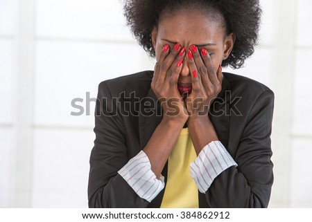 Portrait of mature black unhappy business woman at desk in office - stock photo