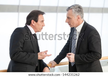 Portrait of mature business man sharing his experience with associate - stock photo