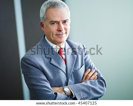 portrait of mature business man with arms folded, looking at camera. Copy space - stock photo