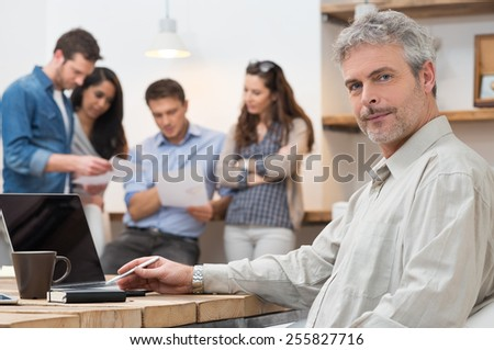 Portrait of mature businessman looking at camera and sitting at desk while workers in background