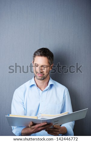Portrait of mature businessman reading in white binder against blue wall - stock photo