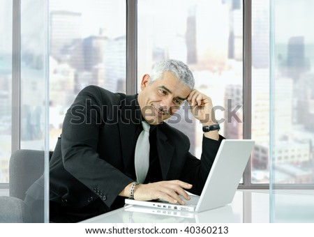 Portrait of mature businessman sitting at desk in orporate office, using laptop computer, smiling. - stock photo