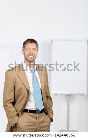 Portrait of mature businessman with hands in pockets standing in office - stock photo