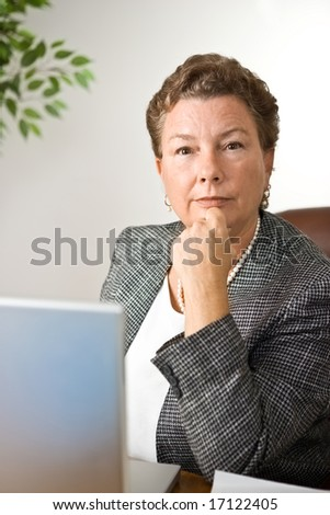 Portrait of mature businesswoman looking with determination straight into the camera - stock photo