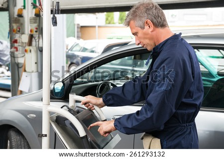 Portrait Of Mature Car Mechanic Working At Service Station - stock photo