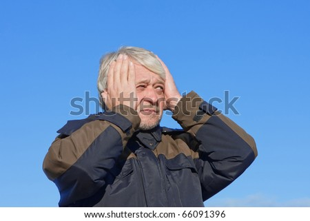 Portrait of mature concerned man with grey hair on blue sky of the background. - stock photo