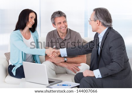 Portrait Of Mature Consultant Shaking Hand With Happy Woman - stock photo