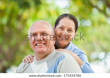 Portrait of mature couple in sweaters at autumn park - stock photo