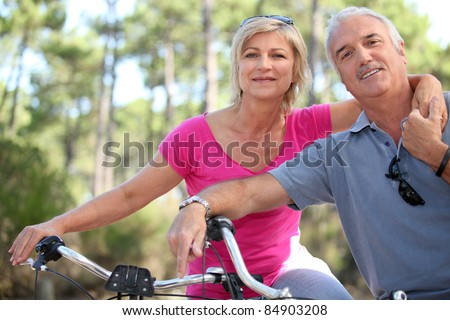 portrait of mature couple on bicycle - stock photo