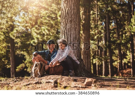 Portrait of mature couple sitting together under a tree with backpacks and compass. Senior man and woman in forest. - stock photo