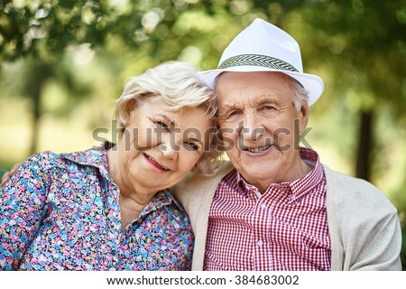 Portrait of mature couple smiling at camera outdoors - stock photo