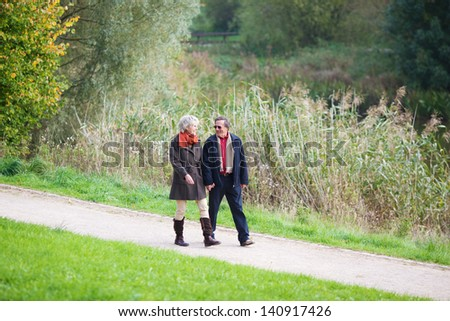 Portrait of mature couple walking holding hands while talking outdoors - stock photo