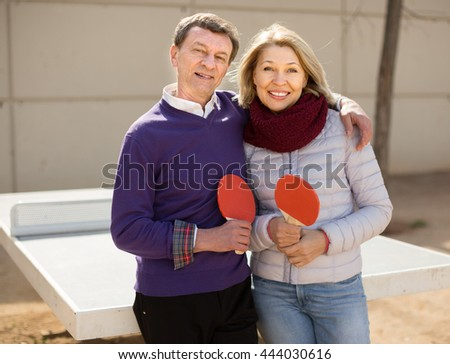 portrait of mature couple with rackets for table tennis