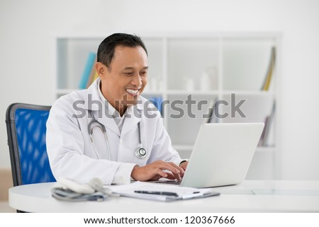 Portrait of mature doctor sitting in his office and typing on laptop - stock photo