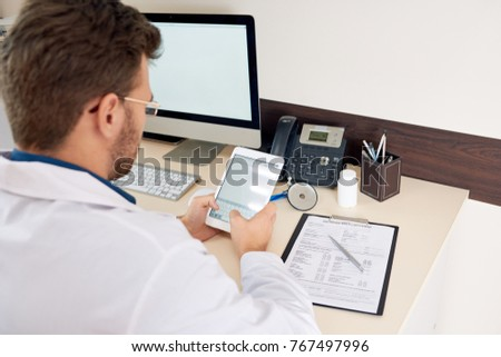 Portrait of mature doctor using digital tablet sitting at desk in office and typing work notes looking at blank white screen