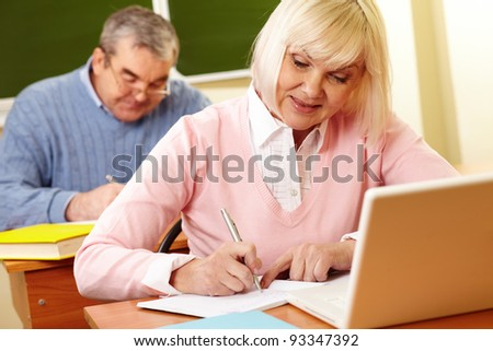 Portrait of mature female making notes in copybook with senior man on background - stock photo