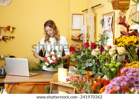 Portrait of mature florist holding a bouquet of flowers in flower shop. Online shopping.  - stock photo