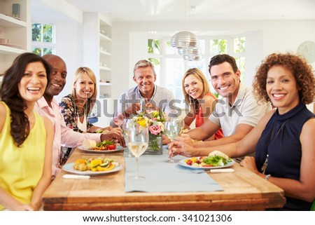 Portrait Of Mature Friends Around Table At Dinner Party - stock photo