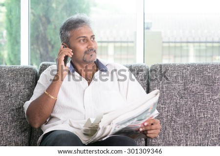 Portrait of mature Indian man calling using smart phone while reading on newspaper, sitting on sofa at home. Asian male relax on couch in house with interior. - stock photo