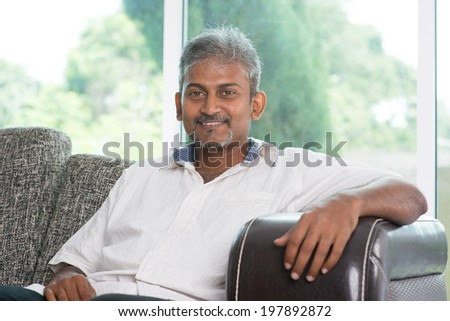 Portrait of mature Indian man sitting on sofa at home. Asian male relax on couch in house with interior. - stock photo
