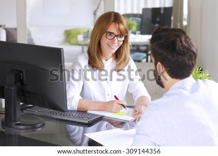 Portrait of mature insurance agent giving advise her new client while sitting at office in front of computer. Businesswoman making financial plan.  - stock photo