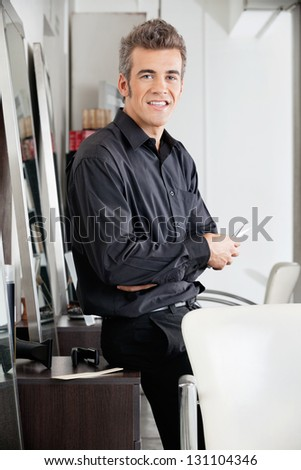 Portrait of mature male hairstylist with scissors leaning on cabinet at hair salon