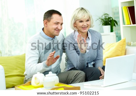 Portrait of mature man and his wife chatting with their friends through internet - stock photo