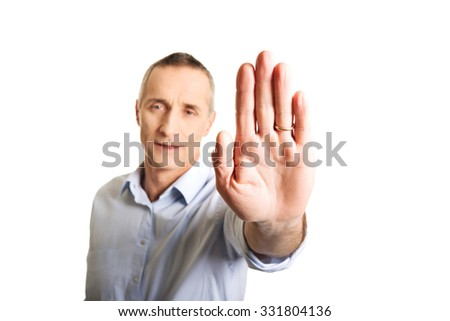Portrait of mature man making stop sign with hand.