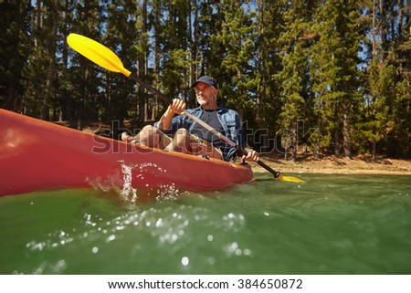 Portrait of mature man paddling a kayak in a lake. Senior caucasian man canoeing on summer day.