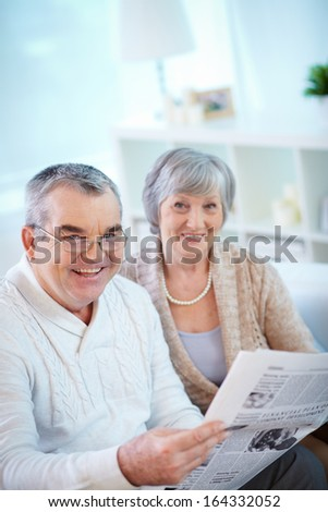 Portrait of mature man reading newspaper at home with his wife near by - stock photo