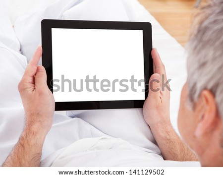 Portrait Of Mature Man Using Digital Tablet - stock photo